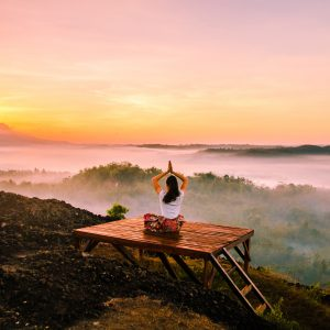 Woman with hands overhead in prayer pose sitting on a platform overlooking a scenic valley at sunset